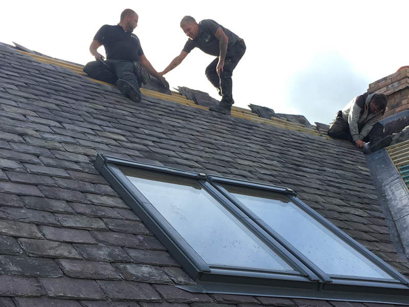 Velux Window on a newly re-slated roof with workmen